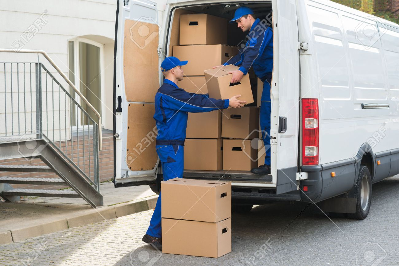 Young delivery men unloading cardboard boxes from truck - 51090575