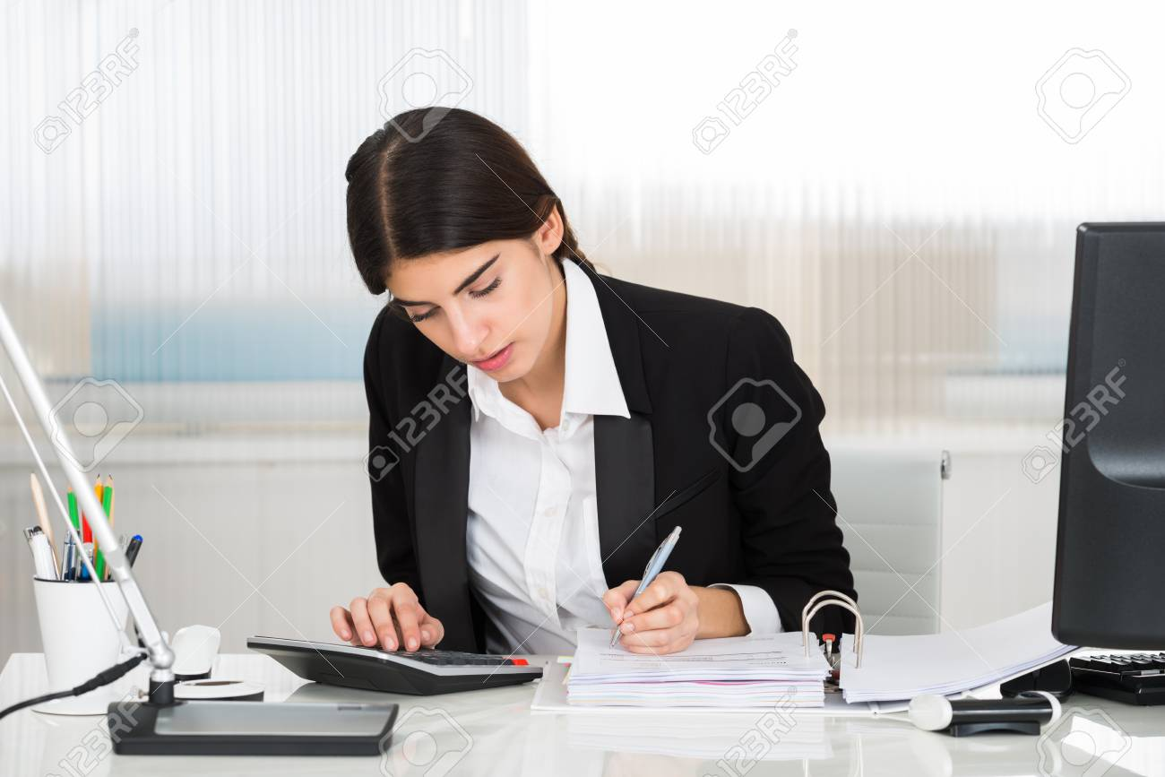 Young Female Accountant Calculating Finance With Calculator At Desk In  Office Stock Photo, Picture And Royalty Free Image. Image 51090625.