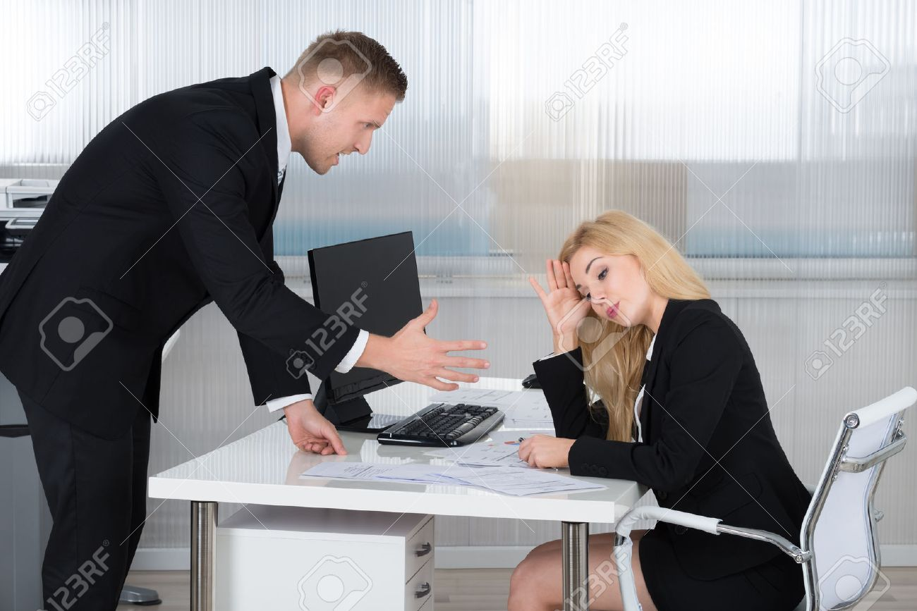 Boss shouting at female employee sitting at desk in office - 51090664