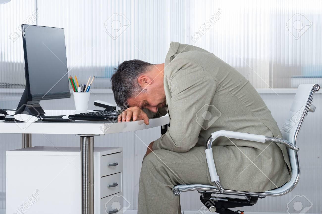 Vue de côté de fatigué d affaires dormir sur un bureau dans le