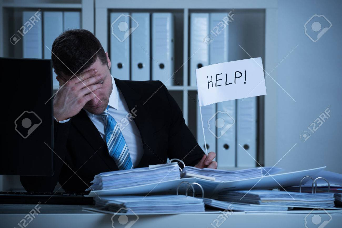 Stressed accountant holding help sign at desk while working late in office - 51090857