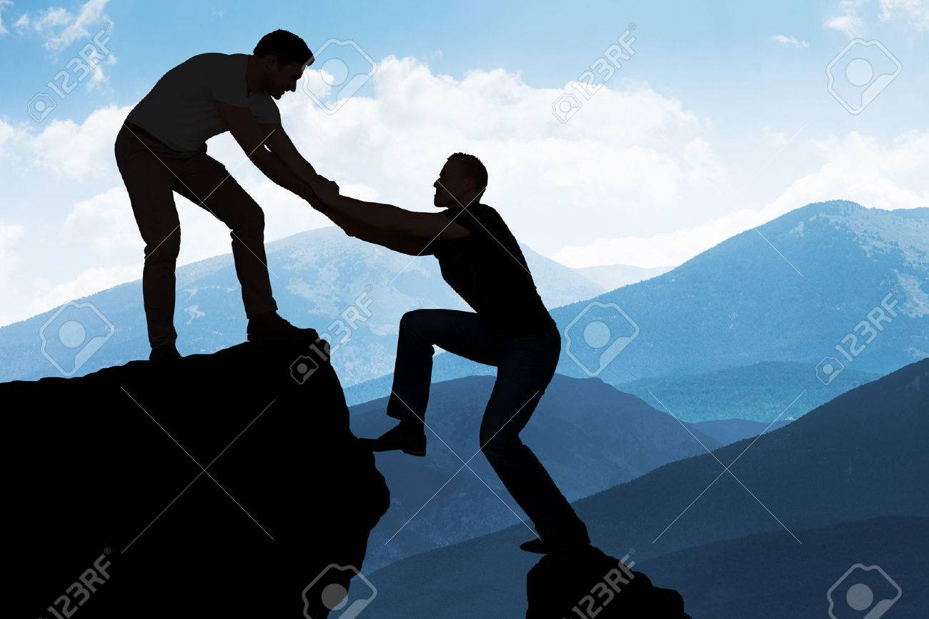 Silhouette young man assisting male friend in climbing rock - 51450665