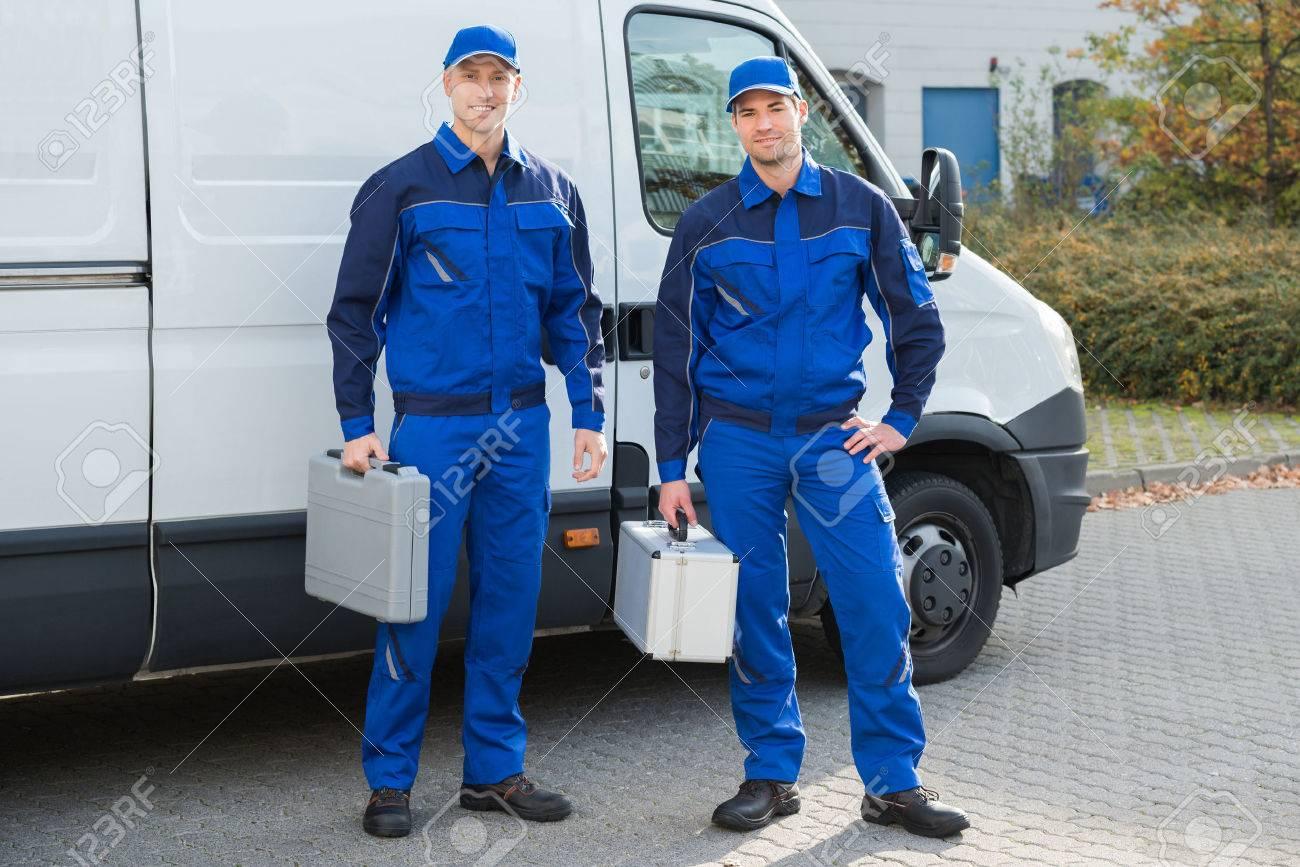 Full length portrait of confident technicians standing against truck on street - 51450673