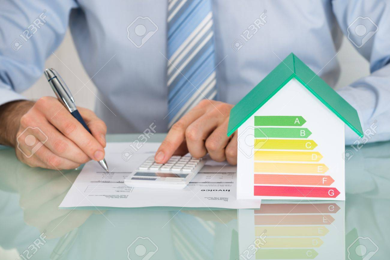 Close-up Of Businessman Calculating Energy Efficiency Rate Of House In Office - 51924965