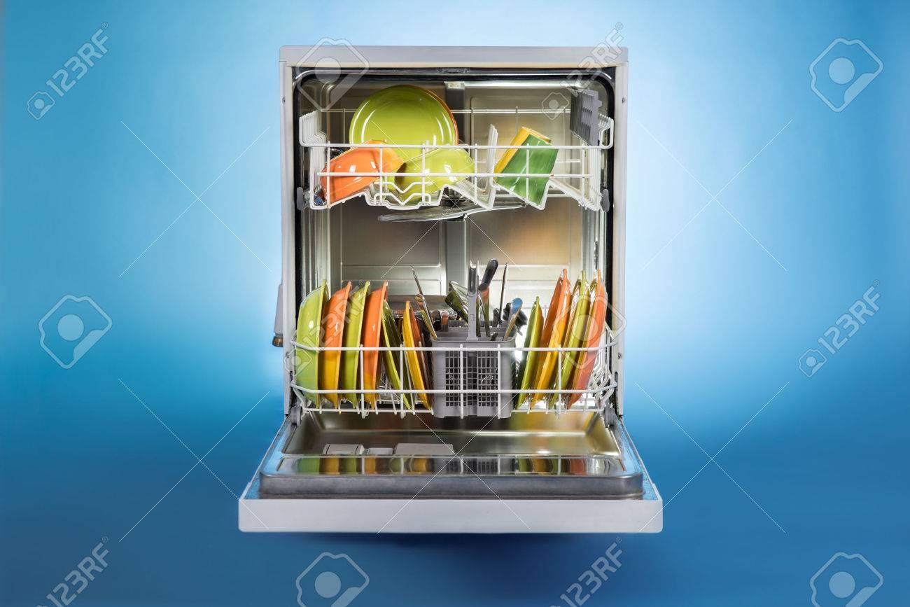 Dishwasher full of utensils isolated against blue background - 51977584