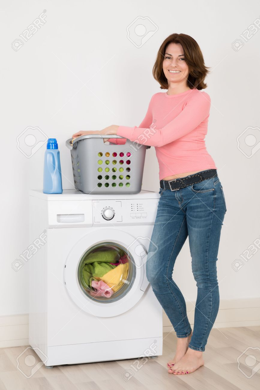Happy Young Woman Standing By Washing Machine With Detergent And Laundry At Home - 52952511