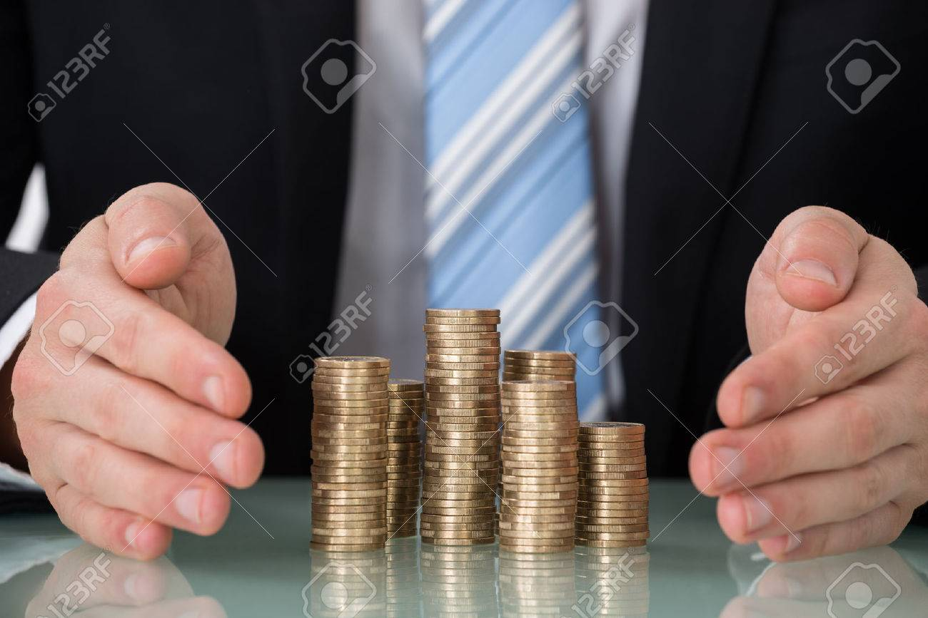 Close-up Of Businessperson Saving Pile Of Coins - 52952376