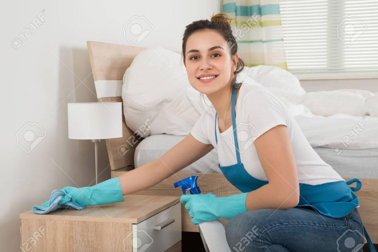 Happy Female Housekeeper Cleaning Nightstand In Room - 53332560