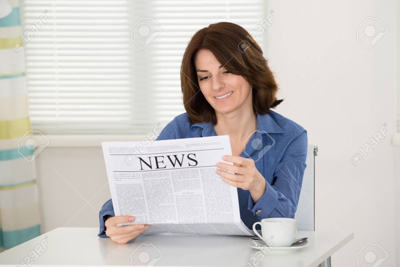 happy young woman reading newspaper at home stock photo, picture and