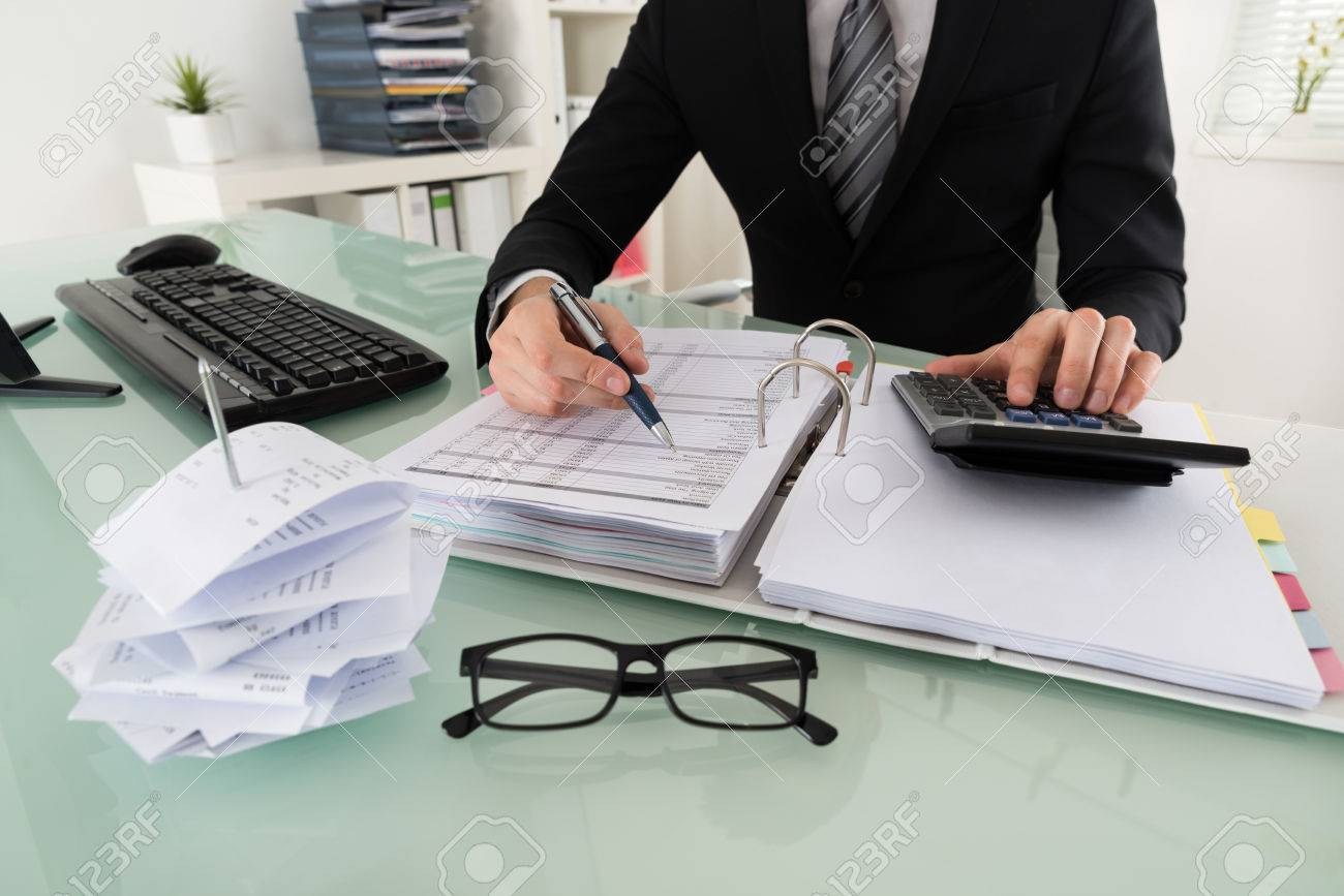 Close-up Of Businessman Calculating Tax In Office - 54191004