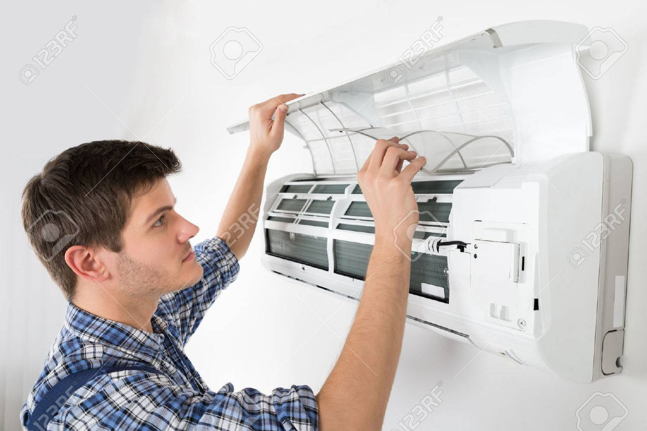young male technician cleaning air conditioning system at home stock