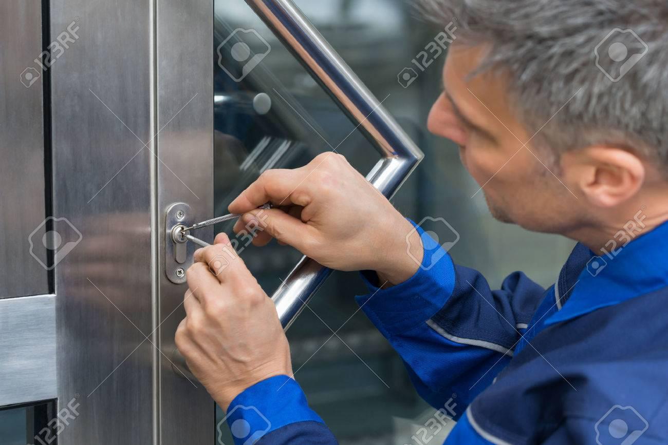 Mature Male Lockpicker Fixing Door Handle At Home - 54599619