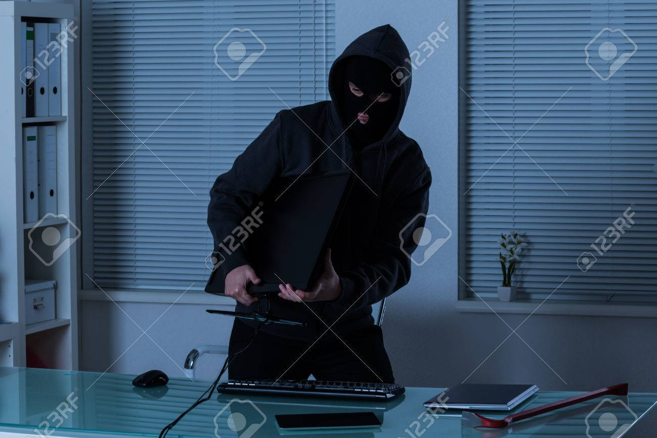 Thief Stealing Computer From Office At Night - 54885513