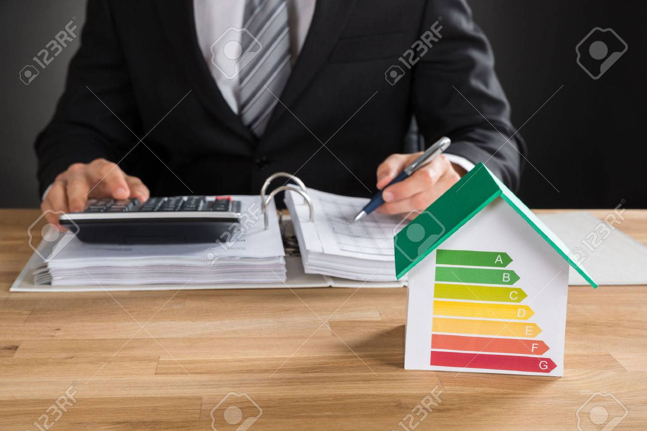 Businessman Calculating Financial Data With House Model Showing Energy Efficiency Rate On Desk - 55430015