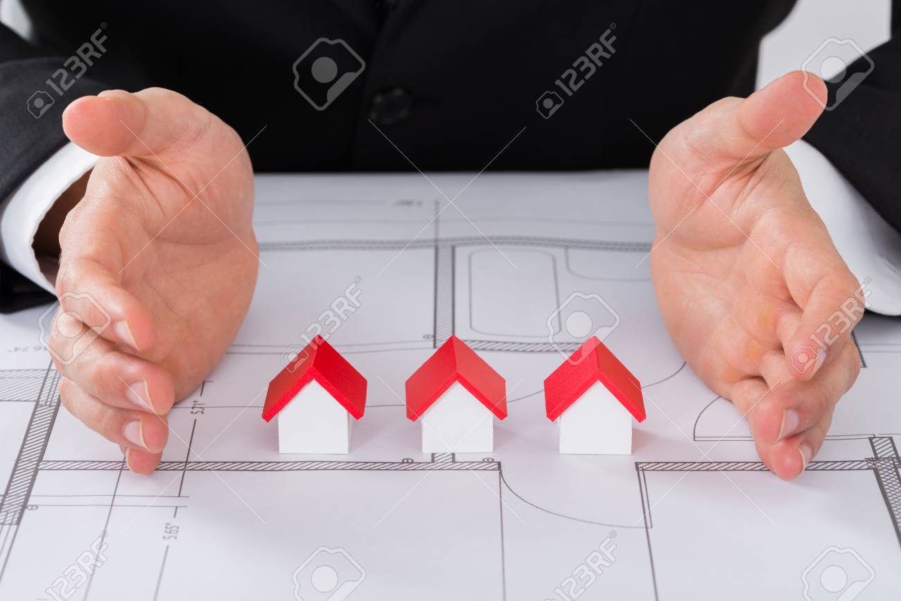 Close up of male architect hand protecting different size of stock close up of male architect hand protecting different size of house models on blueprint stock malvernweather