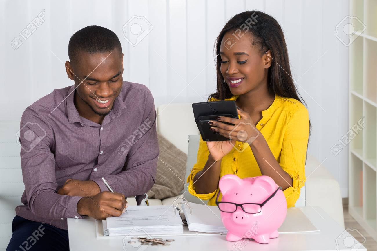 Happy Young Couple Calculating Bill With Coins And Piggybank On Desk - 55666753