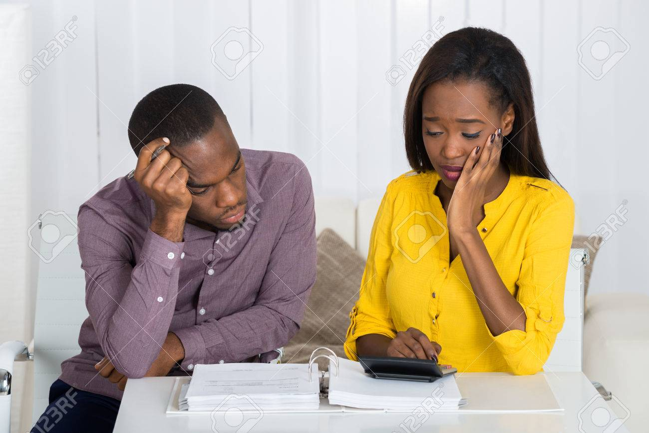 Sad Young African Couple Looking At Bill - 56063946