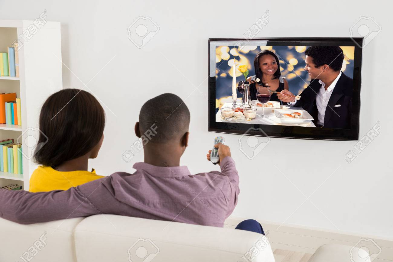 Happy African Couple Watching Television At Home - 56064605