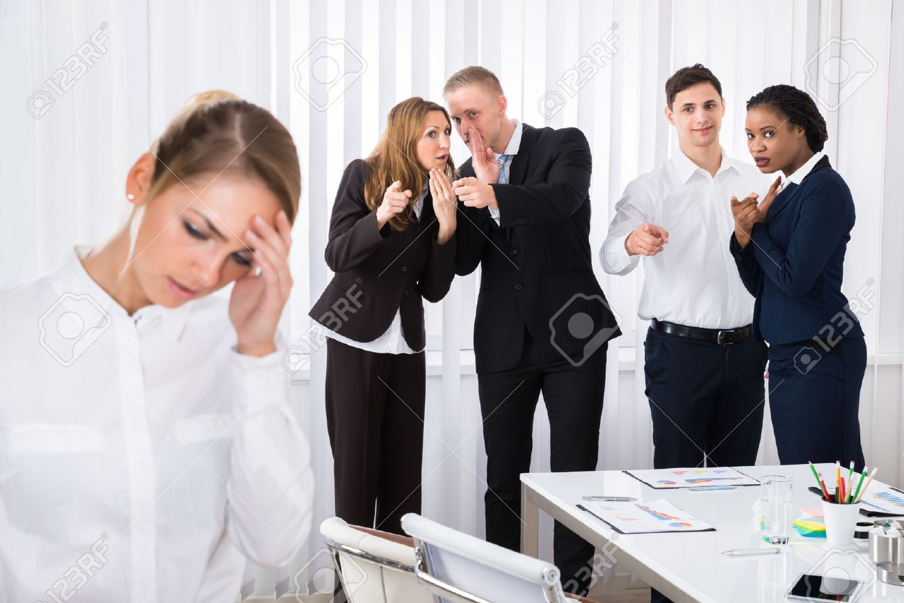 Businesspeople Gossiping Behind Stressed Female Colleague In Office - 56706586