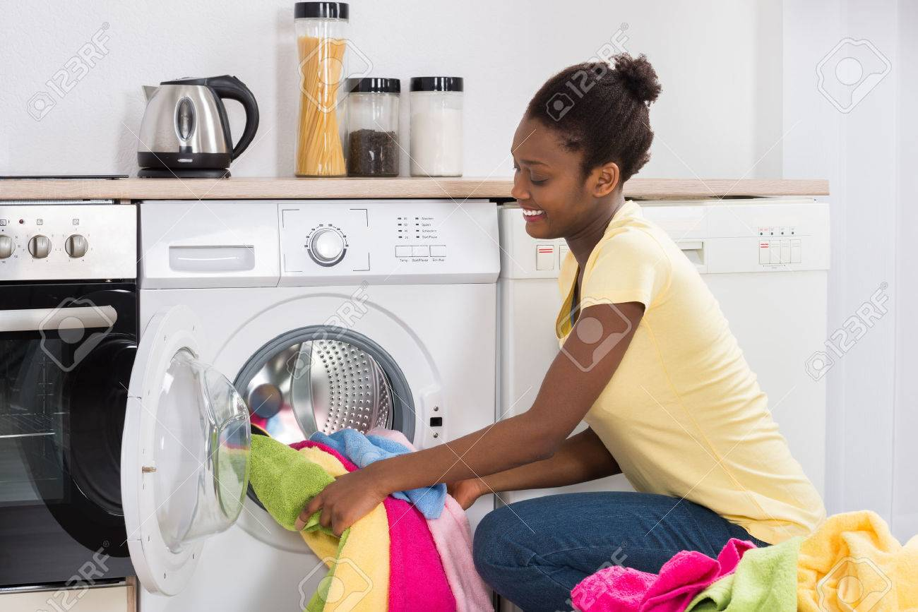 Young African Woman Putting Clothes Into Washing Machine At Home - 56931452