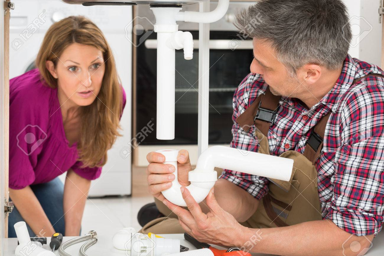 Woman Looking At Mature Male Plumber Fixing Sink Pipe Stock Photo ...