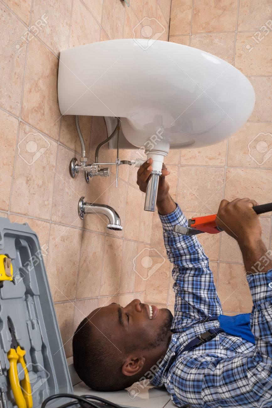 Salle De Bain Qui Pue L'Humidite ~ jeune m le africaine plumber allong sur le sol fixation vier de