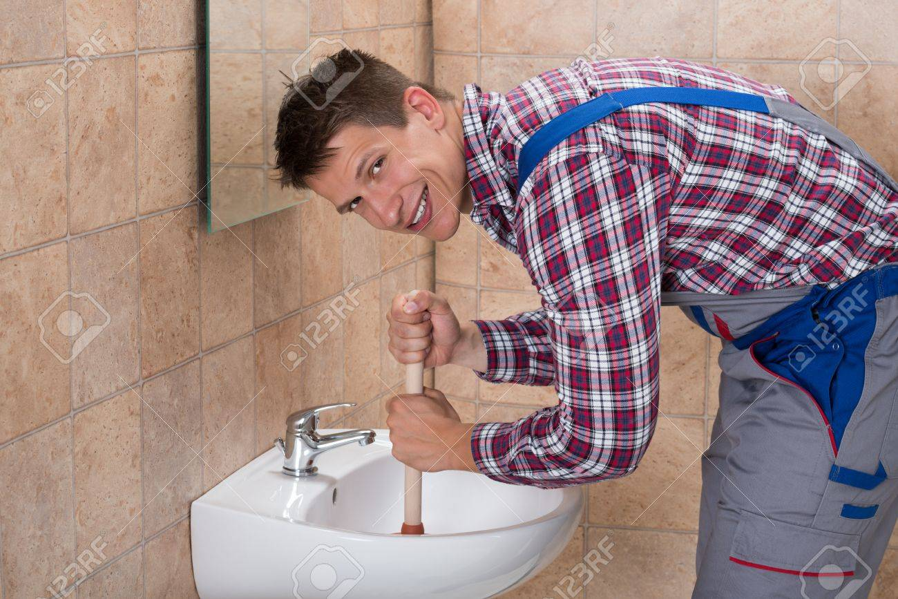 Fine Smiling Young Male Plumber Using Plunger In Clogged Sink In Bathroom Interior Design Ideas Greaswefileorg