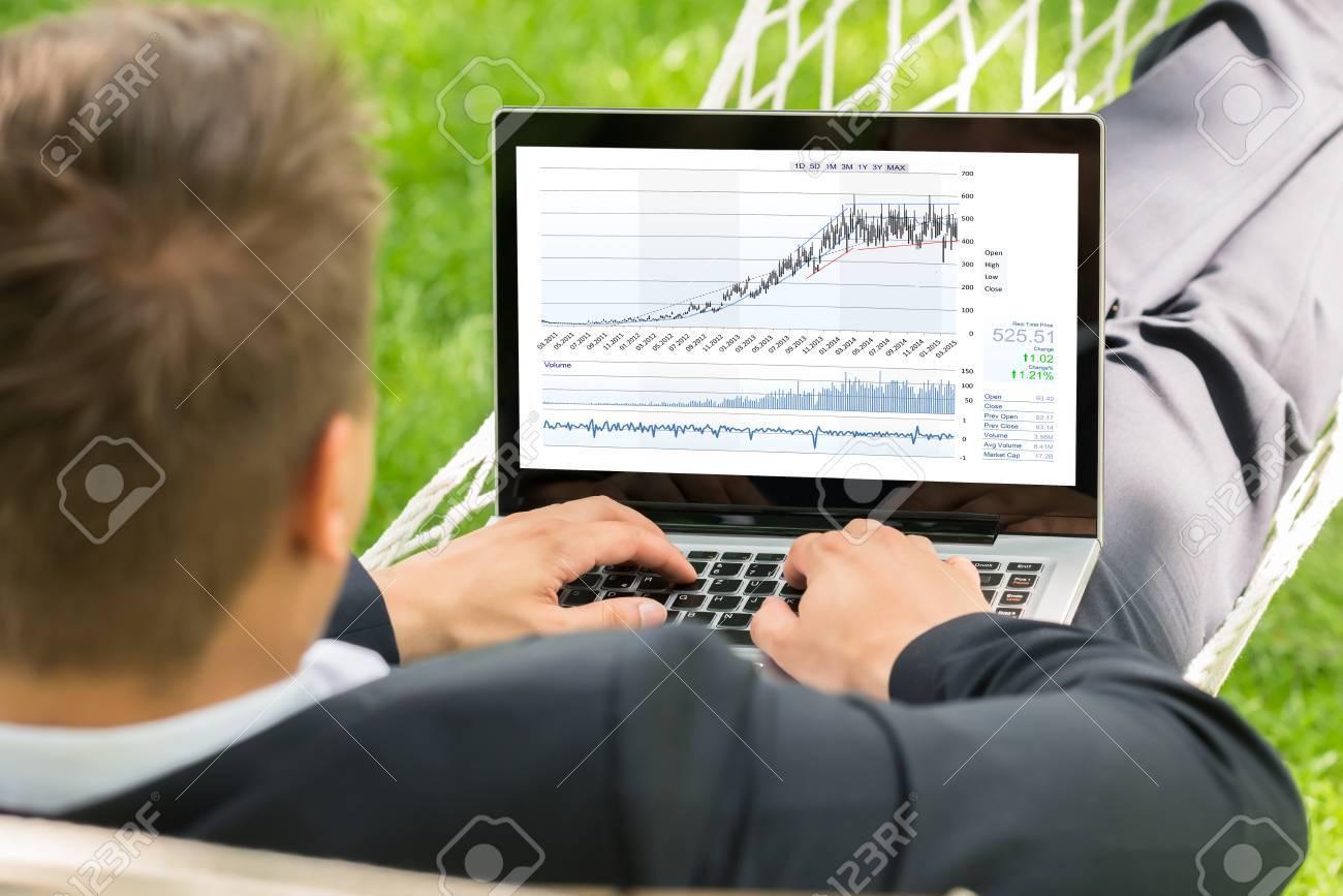 Close-up Of Male Stock Broker Lying In Hammock Using Laptop - 61134931