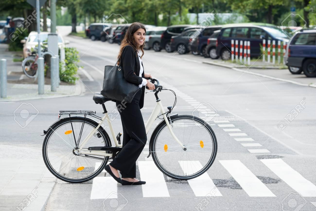 Livraison gratuite dans le monde entier grande qualité femme Vue latérale de la jeune femme souriante avec sac à main, se déplaçant sur  le vélo