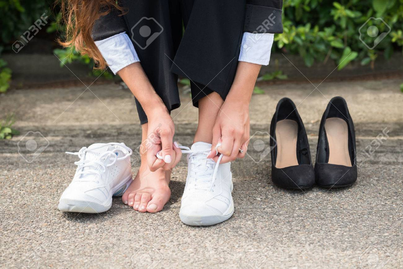 Close-up Of Businesswoman Changing Shoes On Street Standard-Bild - 61135117