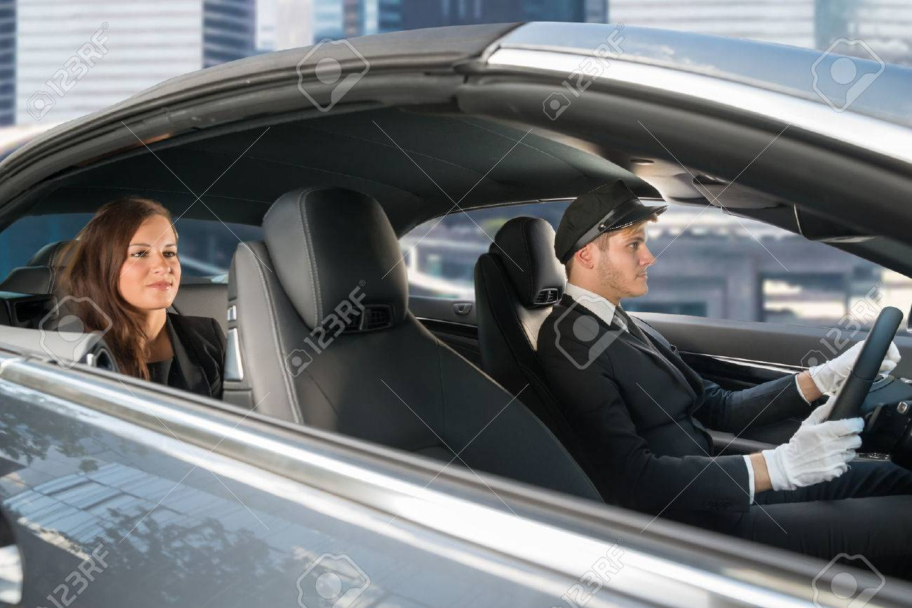 Beautiful Young Woman Traveling In A Car With Male Handsome Chauffeur Standard-Bild - 61135128