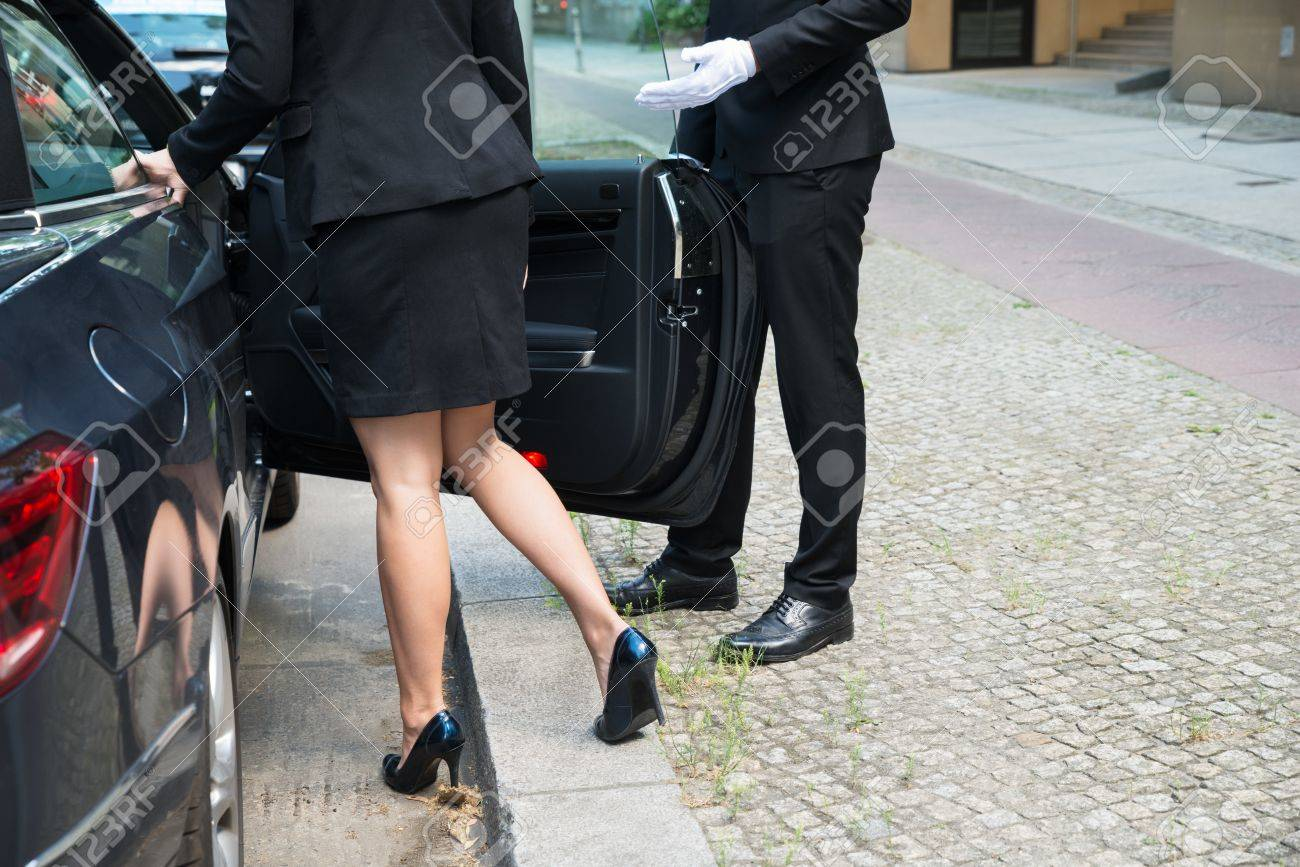 Male Chauffeur Opening The Car Door For The Businesswoman On Street Standard-Bild - 61416911