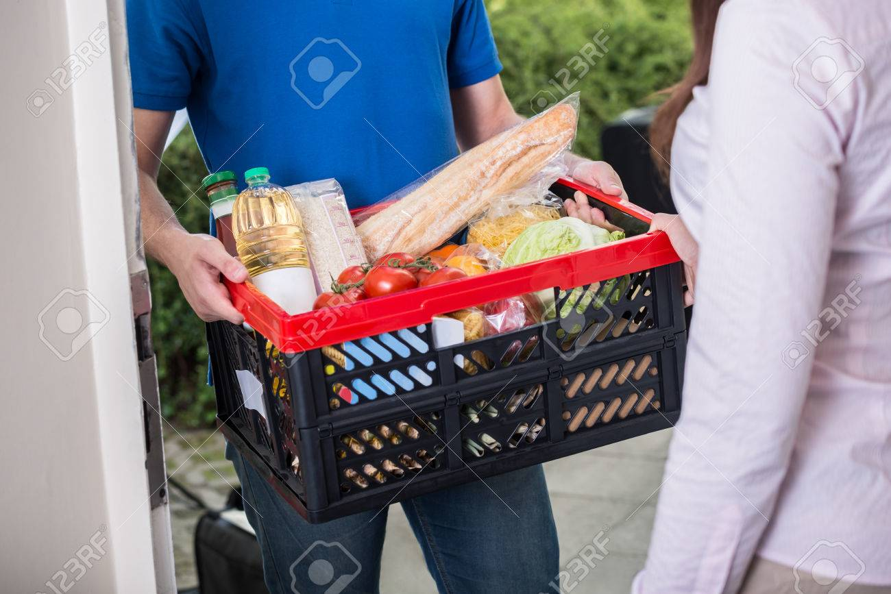 Close-up Of Man Delivers Crate Of Groceries At Home Standard-Bild - 61416926