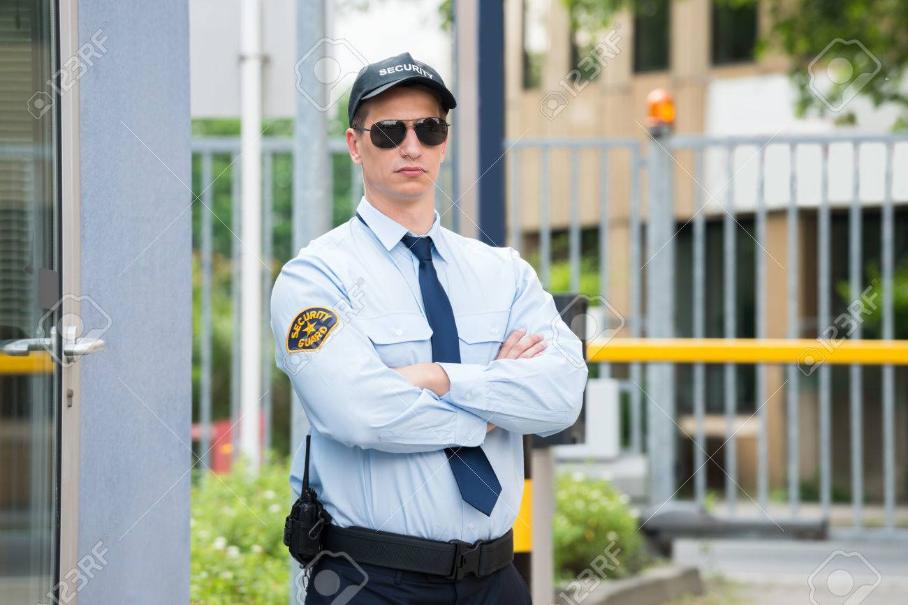 Confident Young Male Security Guard Standing Arm Crossed Standard-Bild - 61416953