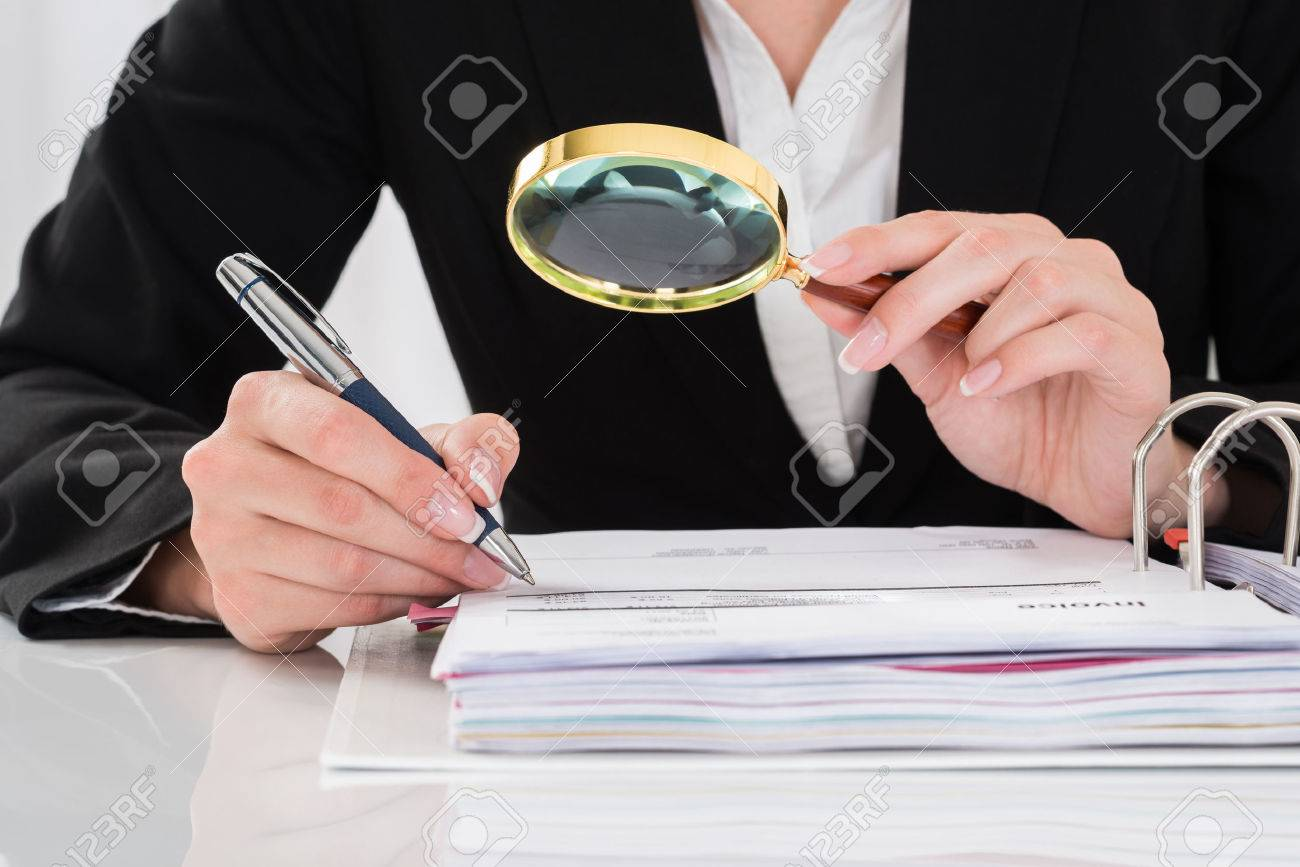 close up of auditor inspecting financial documents at desk stock