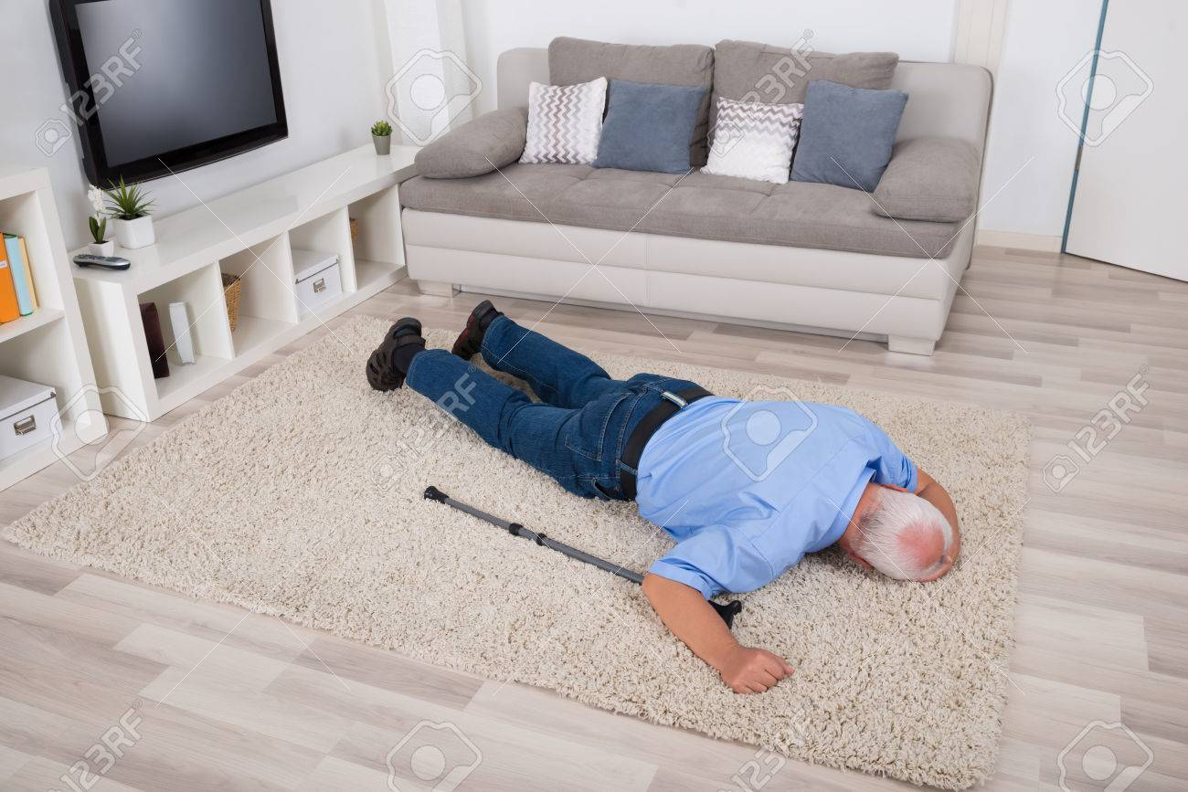 Unconscious Disabled Senior Man Lying On Carpet At Home Standard-Bild - 61867813