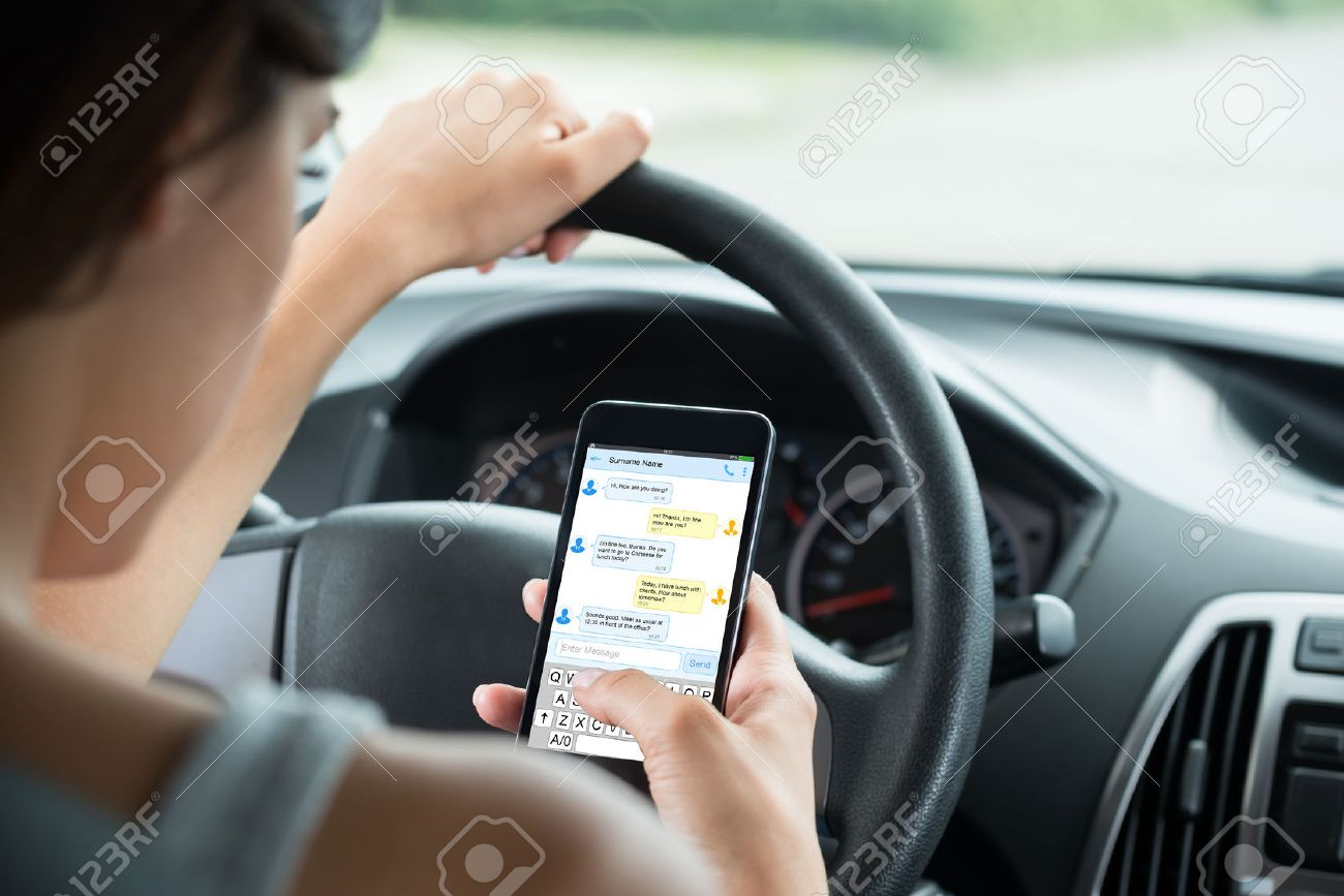 Close-up Of Woman Sitting Inside Car Typing Text Message On Mobile Phone Standard-Bild - 61867865