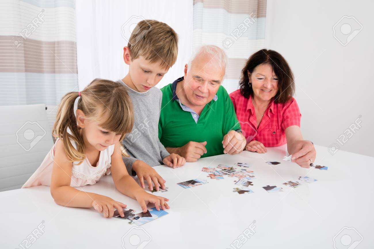 Family Holding Jigsaw Puzzle Pieces While Playing Game Together ...