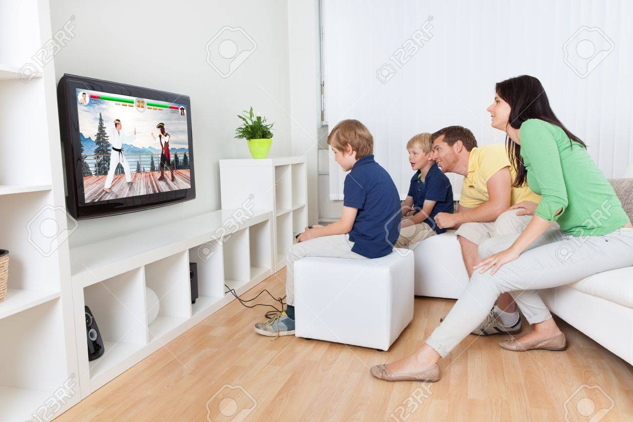 Happy Family Playing Fighting Game On Television At Living Room Stock Photo
