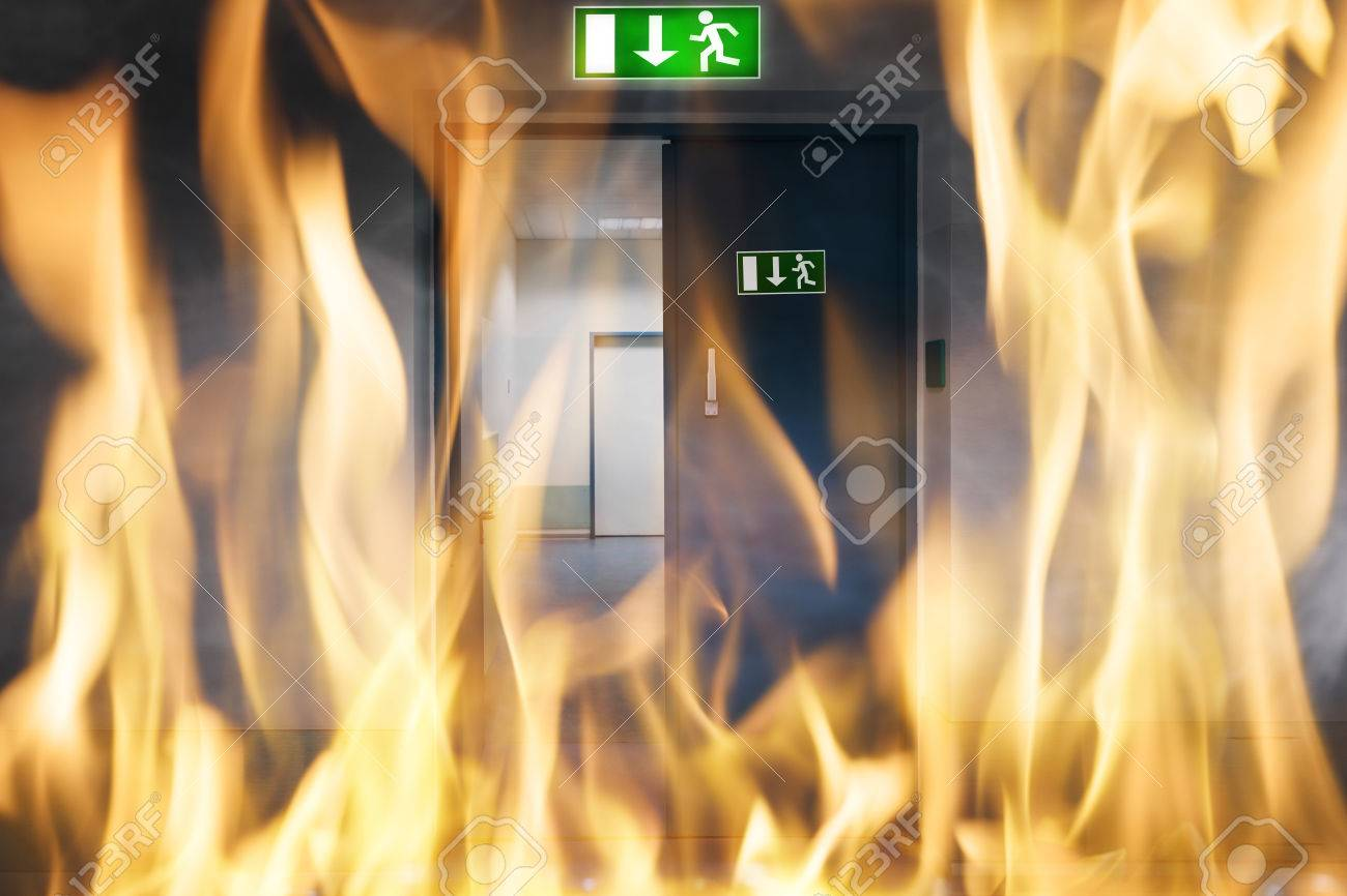Close-up Of Fire Burning Near An Emergency Exit Door Of The Building Standard-Bild - 66970902