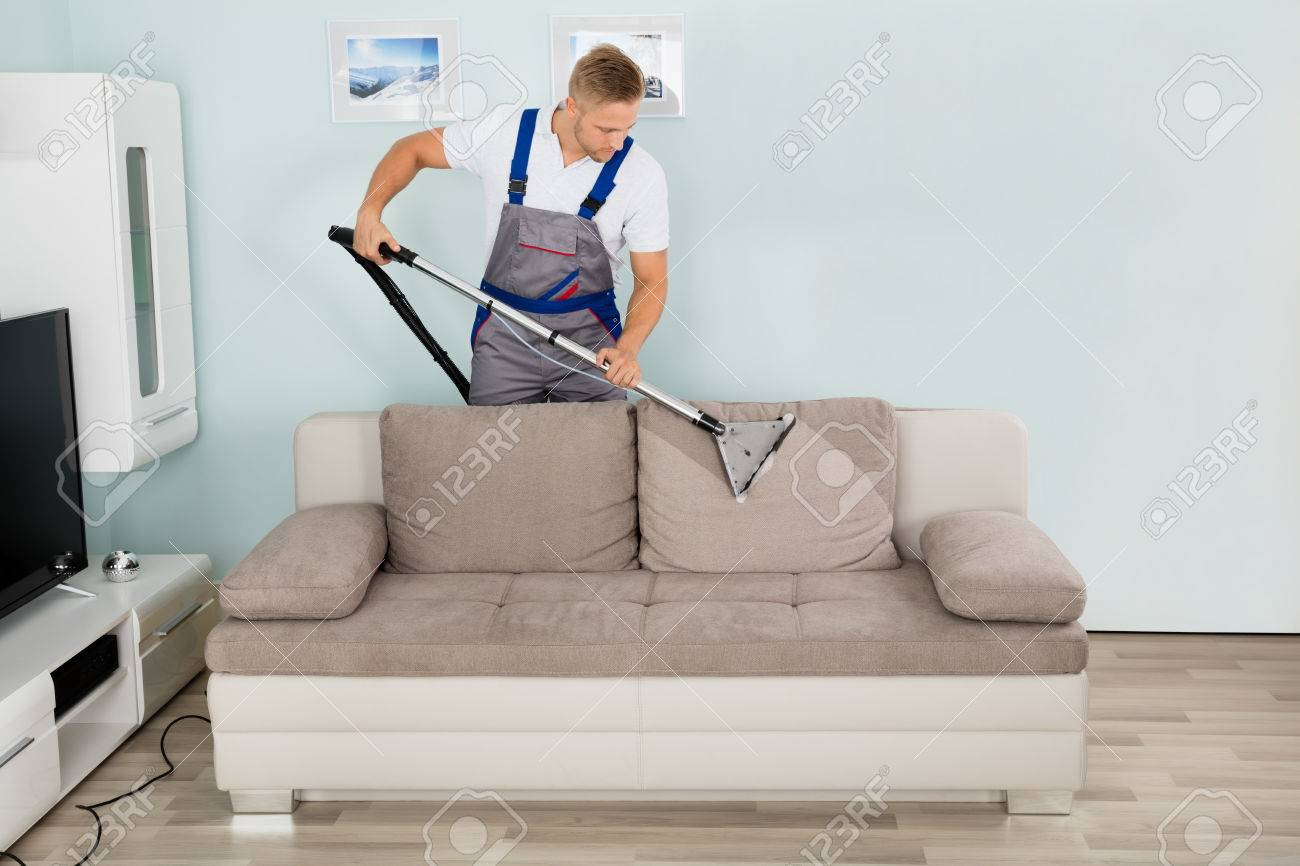 Amazing Stock Photo   Young Male Worker Cleaning Sofa With Vacuum Cleaner
