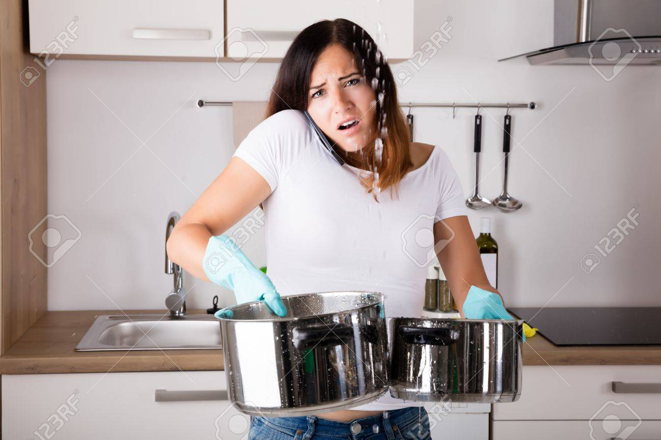 Shocked Woman Calling Plumber While Collecting Water Leaking From Ceiling Using Utensil - 69329767