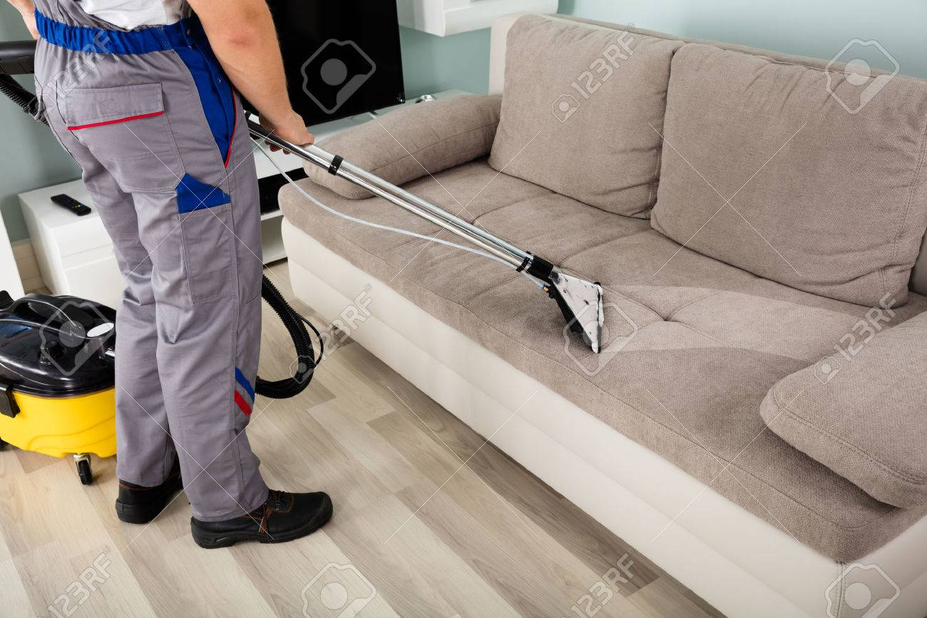 Captivating Rear View Of Young Male Worker Cleaning Sofa With Vacuum Cleaner Stock  Photo   69329780