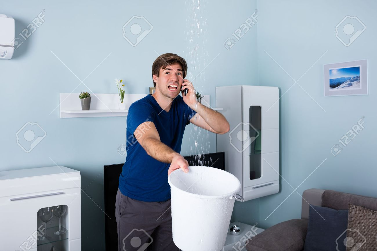 Worried Man Calling Plumber While Leakage Water Falling Into Bucket At Home - 69270448