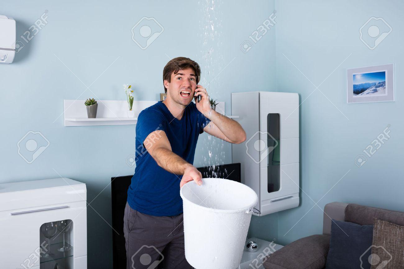 Worried Man Calling Plumber While Leakage Water Falling Into Bucket At Home Standard-Bild - 69270448