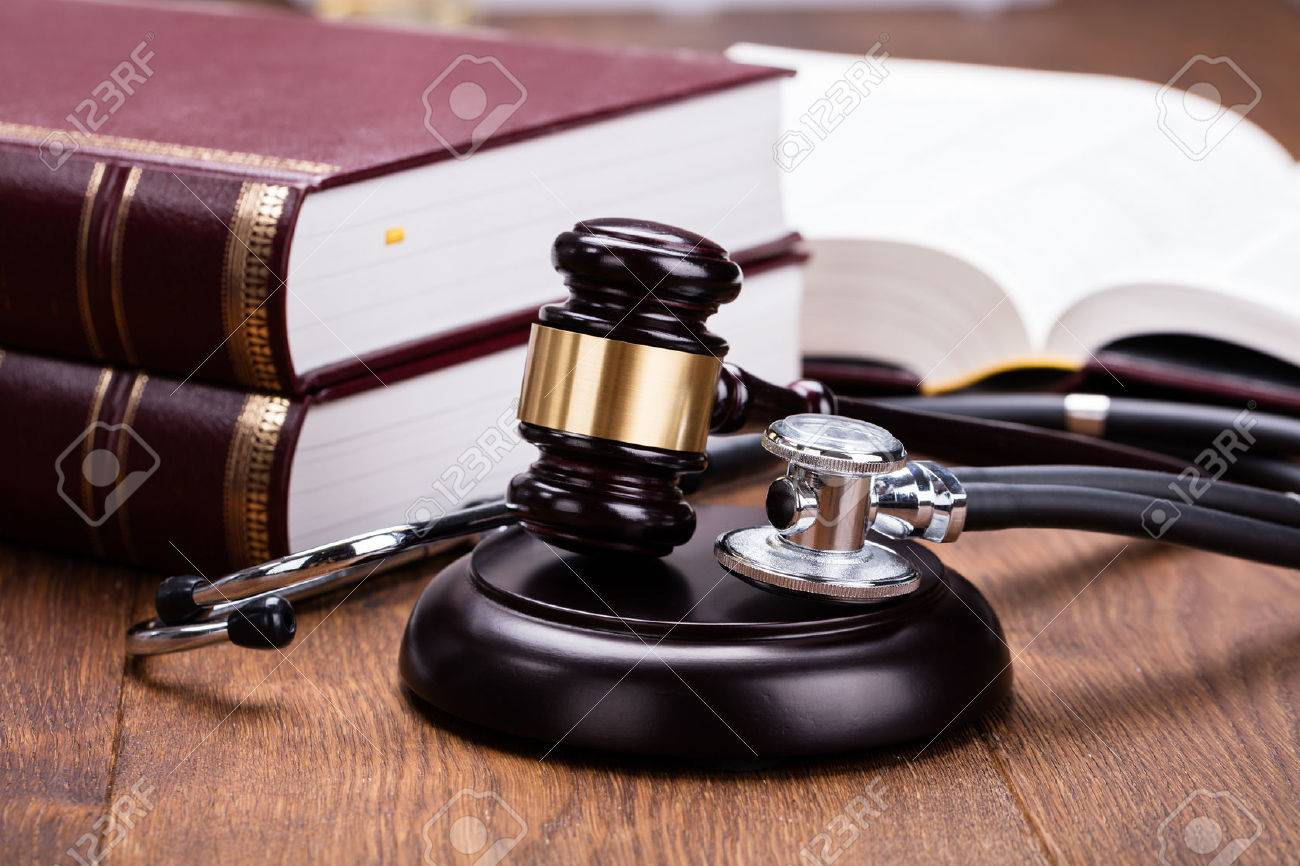 Brown Gavel With Medical Stethoscope Near Book At Wooden Desk In Courtroom - 69428407