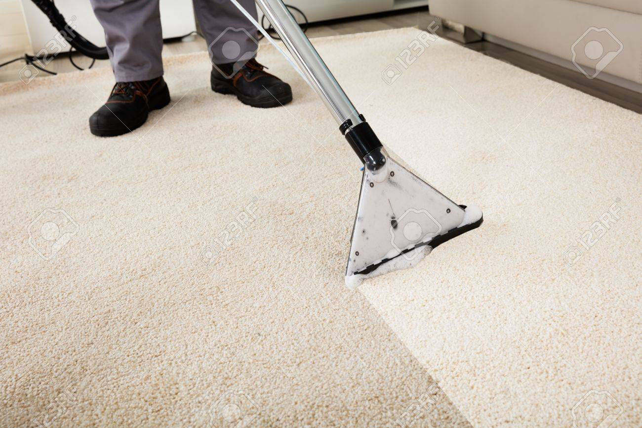Close Up Of A Person Cleaning Carpet With Vacuum Cleaner Stock Photo