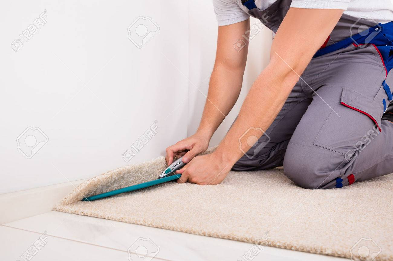 Close-up Of A Craftsman Fitting Carpet On Floor With Cutter Standard-Bild - 69611586