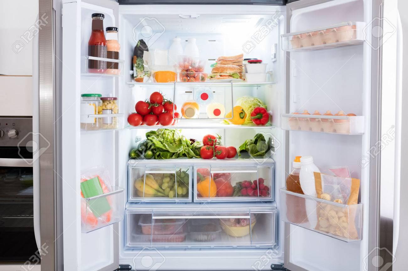 Réfrigérateur ouvert rempli de fruits et de légumes frais Banque d'images - 69611601