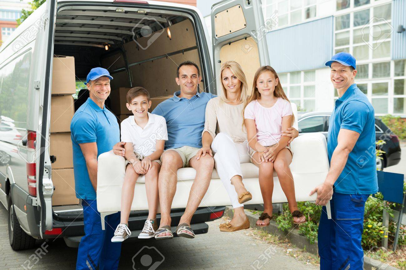 Two Male Happy Furniture Movers Carrying Family On Sofa Out Of
